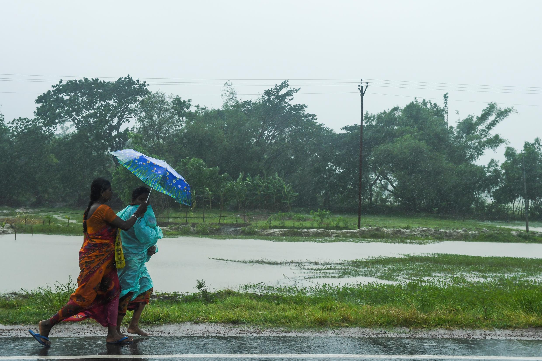 Dos mujeres caminan con un paraguas bajo la lluvia antes de la llegada del ciclón Amphan. Midnapore, Bengala Occidental, India, el 20 de mayo de 2020.