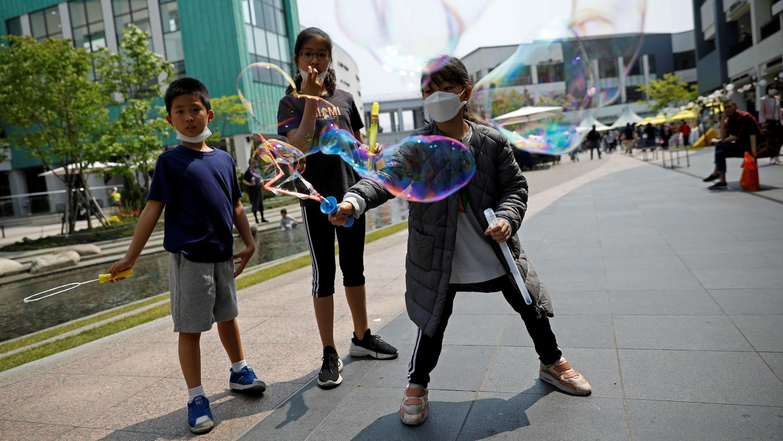 Niños con mascarillas para evitar la propagación del Covid-19 juegan haciendo burbujas en un centro comercial en Gimpo, Corea del Sur, el 1 de mayo de 2020.