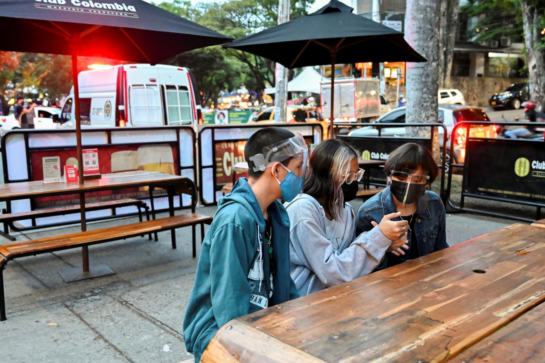 Un grupo de jóvenes usando mascarillas de protección en un restaurante en Cali, Colombia, el 13 de agosto de 2020