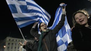 Des supporteurs de Syriza fêtent la victoire de leur parti, dimanche 25 janvier, à Athènes.