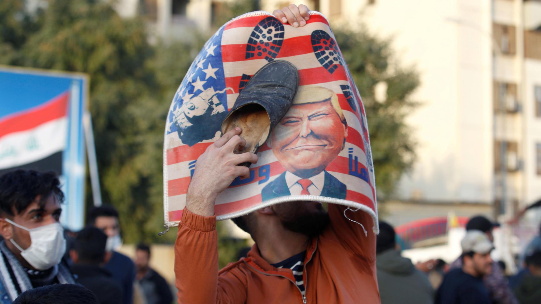 Un manifestante coloca un zapato en una pancarta con la ilustración del presidente de los Estados Unidos, Donald Trump, fuera de la embajada de los Estados Unidos durante una protesta para condenar los ataques aéreos en bases pertenecientes a Hashd al-Shaabi (fuerzas paramilitares), en Bagdad, Irak, el 1 de enero de 2020.