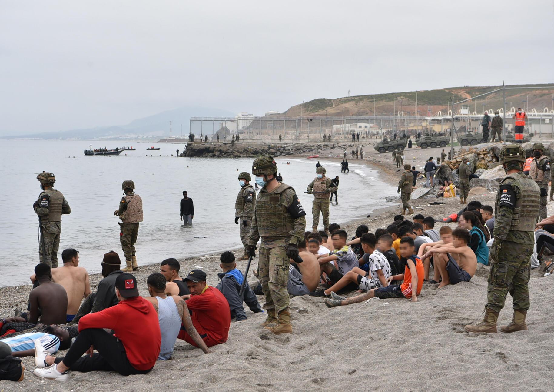 مهاجرون بينهم قصر وصلوا  سباحة من المغرب الى جيب سبتة الاسباني يستريحون امام الجنود الاسبان في 18 أيار/مايو 2021.