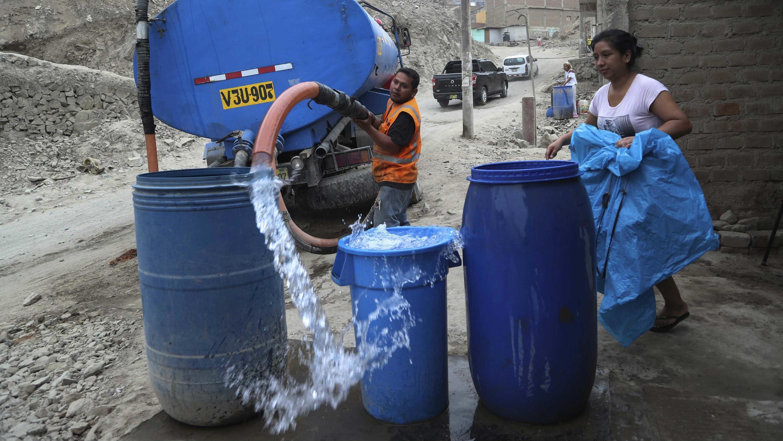 Un trabajador llena un contenedor con agua de un camión cisterna en el barrio marginal de Villa María del Triunfo en Lima, Perú, el 13 de marzo de 2020.