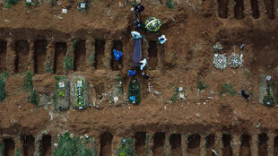 Aerial picture showing gravediggers burying an alleged COVID-19 victim at the Vila Formosa Cemetery, in the outskirts of Sao Paulo, Brazil