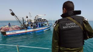 Un membre de la garde nationale tunisienne, à la recherche de migrants illégaux, contrôle un bateau de pêche, en 2015.