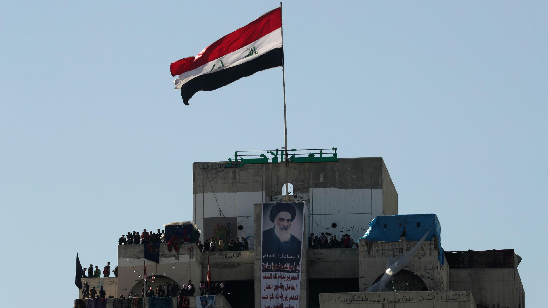 Un cartel del principal clérigo chiita de Iraq, el Gran Ayatolá Ali al-Sistani, es visto mientras los manifestantes iraquíes se paran en el edificio de gran altura, llamado por el Iraquí, el Restaurante Turco, durante las protestas contra el gobierno en Bagdad, Iraq, el 26 de enero. 2020.