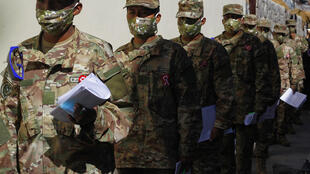 Soldados hacen cola en el Banco de la Nación en Puno, Perú, el 17 de julio de 2020, para cobrar el 'Bono Familiar Universal' -una asignación en efectivo- de 760 soles, equivalente a 216 dólares estadounidenses, proporcionados por el gobierno durante la novela pandemia de coronavirus.
