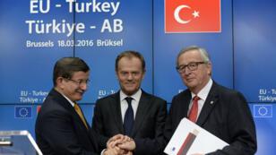 Le Premier ministre turc Ahmet Davutoglu (g.), le président du Conseil européen Donald Tusk (centre) et le président de la Commission européenne, Jean-Claude Juncker, le 18 mars 2016.