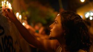 Los manifestantes encienden velas en una pared, frente a la escena del crimen, mientras toman parte en una protesta contra el fusilamiento de la concejal de la ciudad de Río de Janeiro, Marielle Franco, un mes después de su muerte, en Río de Janeiro, Brasil, el 14 de abril de 2018.