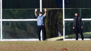 Brazilian President Jair Bolsonaro waves outside Alvorada Palace in Brasilia on July 9, 2020
