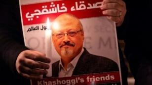 متظاهر يحمل صورة للصحافي السعودي جمال خاشقجي خلال تجمع تكريمي له أمام القنصلية السعودية في إسطنبول، 25 تشرين الأول/أكتوبر 2018