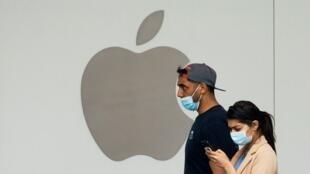 Un comprador usa un teléfono celular mientras camina por una tienda Apple en Arlington, Virginia, Estados Unidos, el 16 de junio de 2020.