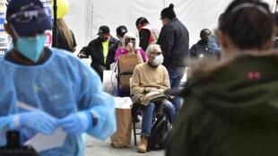 Ancianos vacunados aguardan en una zona de espera antes de salir de un local de distribución de vacunas contra el covid-19 para personas sin techo mayores de 65 años en Los Ángeles