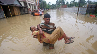 Un policía transporta a una mujer afectada por las inundaciones tras las fuertes lluvias en la aldea de Baldakhal, en las afueras de Agartala, India, el 14 de julio de 2019.