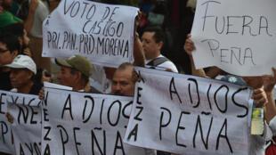 Des manifestants brandissent des pancartes hostiles au président mexicain  Enrique Peña Nieto, à Mexico, le samedi 6 décembre.