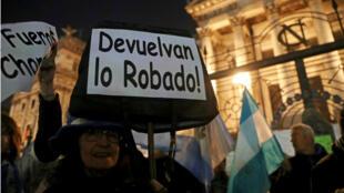 Una mujer sostiene un letrero durante una manifestación contra la corrupción y para exigir al Senado que retire de la inmunidad a la expresidenta y senadora argentina Cristina Fernández de Kirchner, en Buenos Aires, Argentina, el 21 de agosto de 2018.