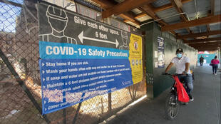 Masked cyclist rides past a sign instructing people how to stay safe as New York City enters phase one of reopening after its Covid-19 lockdown, Harlem, NYC, June 8, 2020.