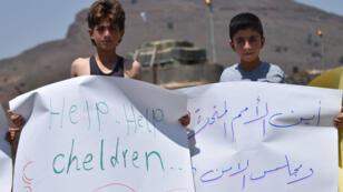 أطفال سوريون نازحون يحملون لافتات خلال مظاهرة أمام قاعدة في محافظة القنيطرة، يطالبون الأمم المتحدة بمساعدة النازحين في سوريا والأردن بفتح حدوده، 4 تموز/يوليو 2018.