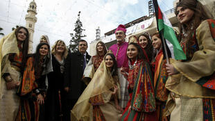 Archbishop Pierbattista Pizzaballa (C), Apostolic Administrator of the Latin Patriarchate of Jerusalem, poses in a group picture with Palestinian women and girls dressed in traditional clothing at the Manger Square outside the Church of the Nativity in the West Bank city of Bethlehem on December 24, 2017.