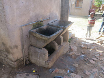 The Mahlangu family share this washbasin with 15 other families in the township. They use it do their dishes and laundry and also to collect water for cooking and drinking.