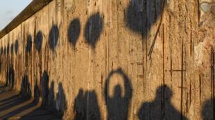 Les ombres de passants et de l'installation lumineuse Lichtgrenze sont projetées sur le mémorial de l'ancien Mur de Berlin sur la Bernauer Strasse, samedi 8 novembre.