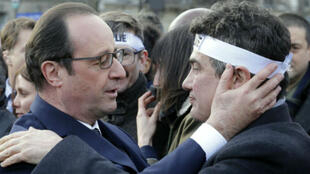 Philippe Wojazer, AFP l Hollande embraces Charlie Hebdo survivor Patrick Pelloux during the January 11 mass rally in Paris
