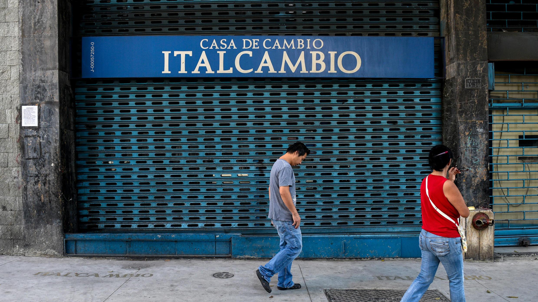 Personas caminando frente a una casa de cambio cerrada en Caracas, el 20 de agosto de 2018.