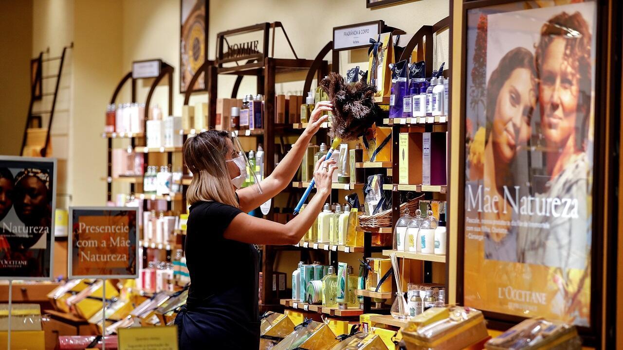 La empleada de un negocio limpia el local al interior de un centro comercial en Sao Paulo (Brasil), tras la reapertura de sus puertas, el 11 de junio de 2020.