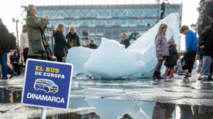 Personas toman fotos de la instalación del artista danés Olafur Eliasson, representando 12 enormes trozos de la capa de hielo de Groenlandia, frente a la Alcadía de Copenhague, el 26 de octubre de 2014.