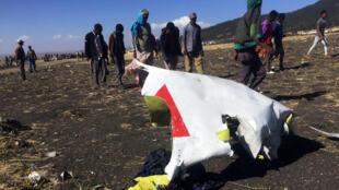Un grupo de personas camina cerca de los restos del avión de Ethiopian Airlines que cubría el vuelo ET 302 en Bishoftu, Etiopía, el 10 de marzo de 2019.