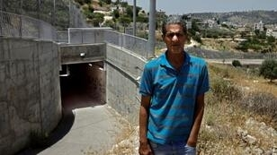 Palestinian Omar Hajajla stands in front of the tunnel that connects Jerusalem to his village in the occupied West Bank