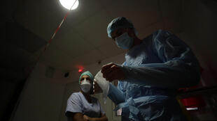 A medical worker prepares to enter the room of a patient suffering from the coronavirus disease in the Intensive Care Unit at the Clinique Bouchard-ELSAN private hospital in Marseille, France, September 21, 2020.