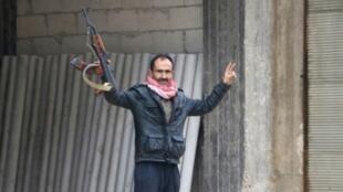 رجل يرفع سلاحه وشارة النصر في بلدة جنديرس الكردية في منطقة عفرين شمال سوريا في 24 كانون الثاني/يناير 2018