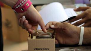 Una votante marca su dedo con tinta como símbolo del ejercicio de sufragio en la jornada electoral en San Salvador, El Salvador, el 4 de marzo de 2018.