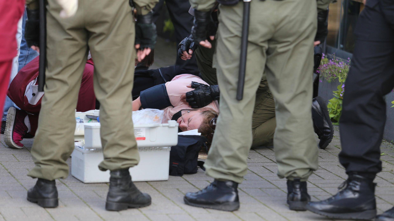 Los agentes rodean a una mujer que recibe tratamiento médico durante una manifestación contra el Gobierno en Minsk, Belarús, el 19 de septiembre de 2020.
