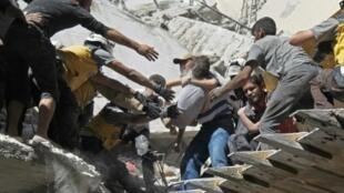 عناصر من الخوذ البيضاء مع مدنيين يعملون على سحب ضحايا من تحت أنقاض منزل تعرض لقصف الطيران السوري في مدينة أريحا في محافظة إدلب في 27 أيار/مايو 2019