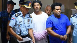 Juez dictamina que Ronaldinho debe permanecer en la cárcel paraguaya - Corte Suprema Paraguaya, Asunción, Paraguay - 7 de marzo de 2020 Ronaldinho y su hermano Roberto de Asís esposados y escoltados por la policía en la Corte Suprema de Paraguay