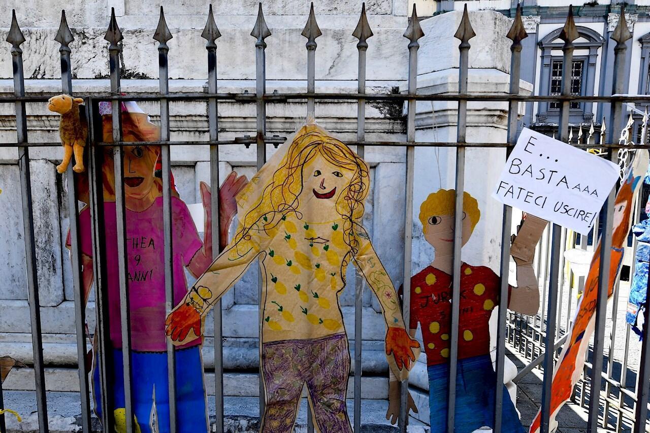 Dibujos de niños en cartulinas y algunos mensajes fueron ubicados en el recinto de la estatua de Dante Alighieri en la plaza homónima de Nápoles, Italia, el 27 de abril de 2020.