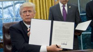 Trump signe le retrait des États-Unis de l'accord de partenariat transpacifique, le 23 janvier 2017 à Washington.