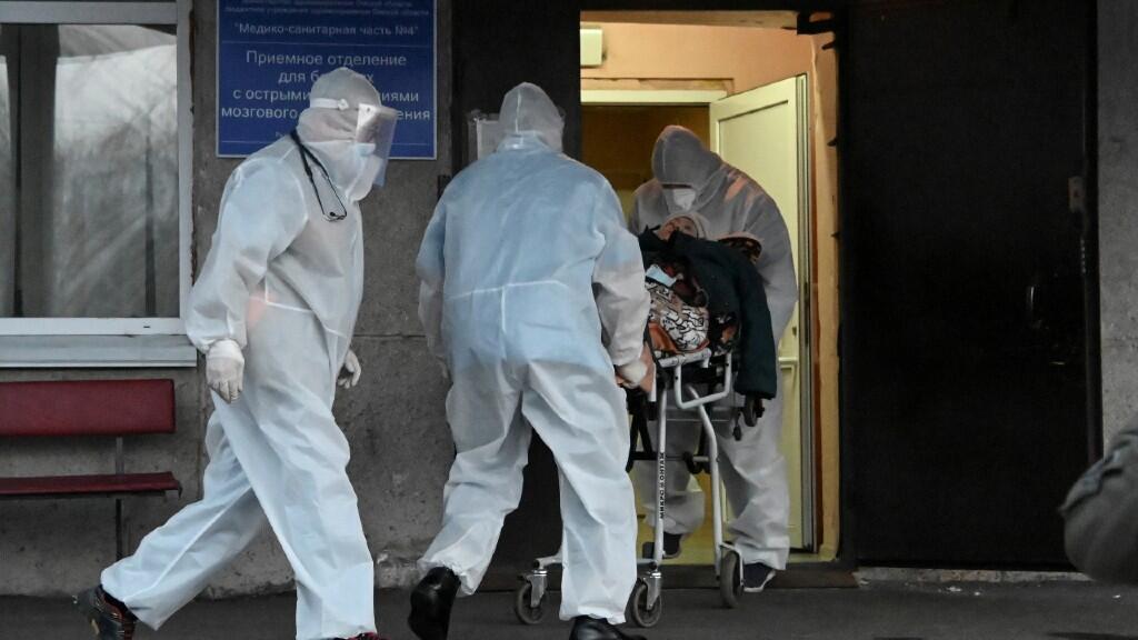 Los paramédicos que usan equipo de protección personal (EPP) empujan una camilla mientras transportan a un paciente a un hospital en Omsk, Rusia, el 28 de octubre de 2020.