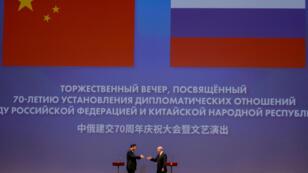El presidente chino Xi Jinping y el presidente ruso Vladimir Putin se dan la mano durante una ceremonia dedicada al 70 aniversario del establecimiento de relaciones diplomáticas entre Rusia y China en el Teatro Bolshoi de Moscú, Rusia, 5 de junio de 2019.