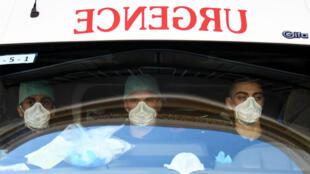 Des ambulanciers portent des masques avant de prendre en charge un patient atteint du nouveau coronavirus, le 24 mars à Paris.