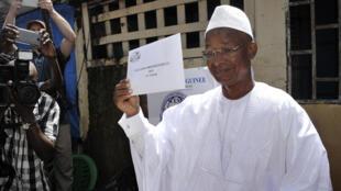 Le président guinéen, Alpha Condé, montre son bulletin de vote, dimanche 11 octobre 2015, lors du premier tour de l'élection présidentielle en Guinée.