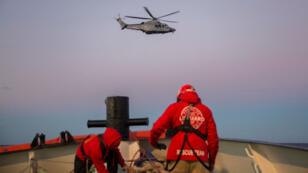 Une mère et son bébé sont évacués par un hélicoptère après avoir été secourus avec près de 300 autres migrants au large de la Libye, le 21 décembre 2018.