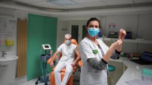 Une infirmière se prépare à administrer le vaccin de Pfizer-BioNTech au Dr Jean-Christophe Richard à l'hôpital de la Croix-Rousse, à Lyon, le mercredi 6 janvier 2021.