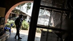 A police officer stands guard beside a window full of bullet holes at an Ebola treatment centre in Butembo. Suspected Mai-Mai tribal militia raided the ETC and killed a policeman and wounded a health worker early in March