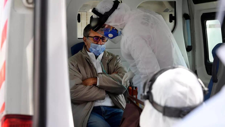فريق طبي يتابع مريضا مصابا بفيروس كوفيد-19 داخل سيارة إسعاف في العاصمة تونس في 6 نيسان/أبريل 2020