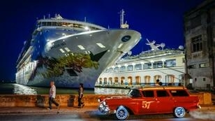 "An old American car passes the ""Empress of the Seas,"" a Bahamas-flagged vessel owned by US Royal Caribbean, which in June 2019 became the last cruise of a US company to stop at the Cuban port of Havana following new US sanctions"