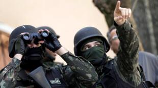 Un miembro de las fuerzas armadas mira a través de unos binoculares durante una operación contra bandas de narcotraficantes en el barrio Morro dos Macacos en Río de Janeiro, Brasil 6 de octubre de 2017.
