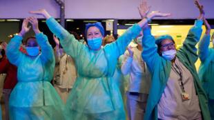 أفراد الطواقم الطبية الذين يعالجون المصابين بفيروس كوروناالمستجد يصفقون للناس الذين يحيونهم وهم يخرجون من مستشفى لا في في فالنسيا بإسبانيا في 26 آذار/مارس 2020